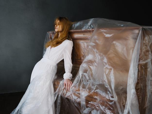 Femme près du piano en robe blanche posant la romance