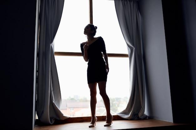 Femme près de la fenêtre en robe noire et posant