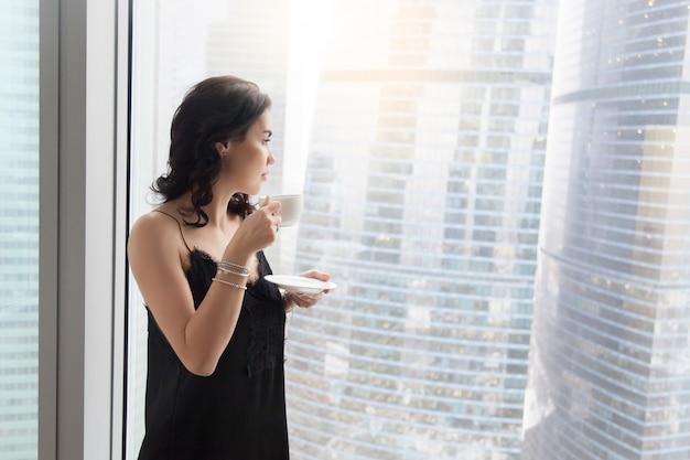 Femme près de la fenêtre