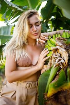Femme près de grande feuille verte de bananier sur la nature dans le parc. plantes tropicales