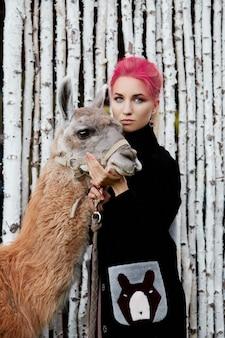 Femme près de lama en automne sur des bouleaux