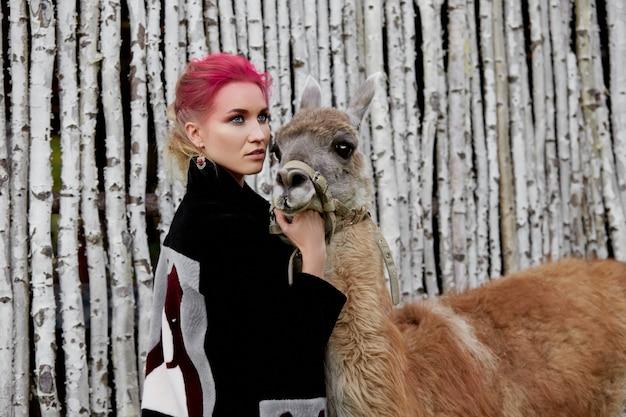 Femme près de lama contre les bouleaux.