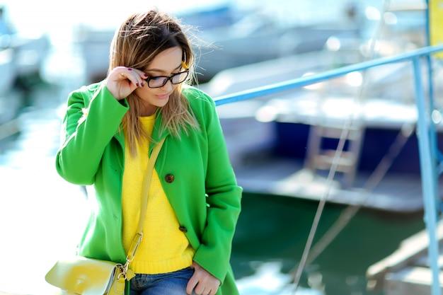 Une femme près de la mer avec des cheveux blonds et des lunettes de soleil se promène au début de l'automne