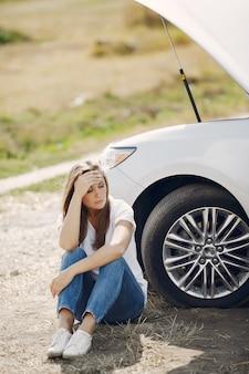 Femme près d'une voiture cassée appeler à l'aide