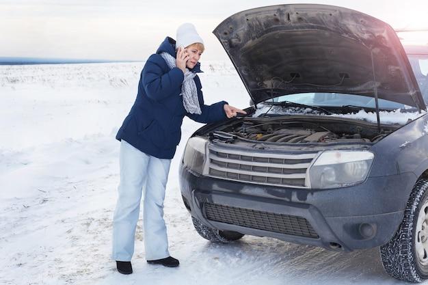 Une femme près d'une voiture cassée essayant de réparer le moteur. elle est au téléphone. elle a froid. autour de l'hiver et du champ de neige.
