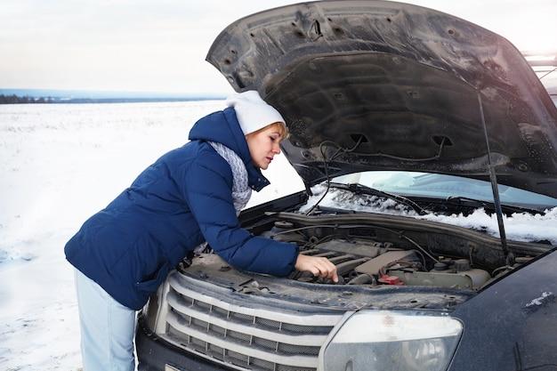 Une femme près d'une voiture cassée essayant de réparer le moteur. elle a froid. autour de l'hiver et du champ de neige.