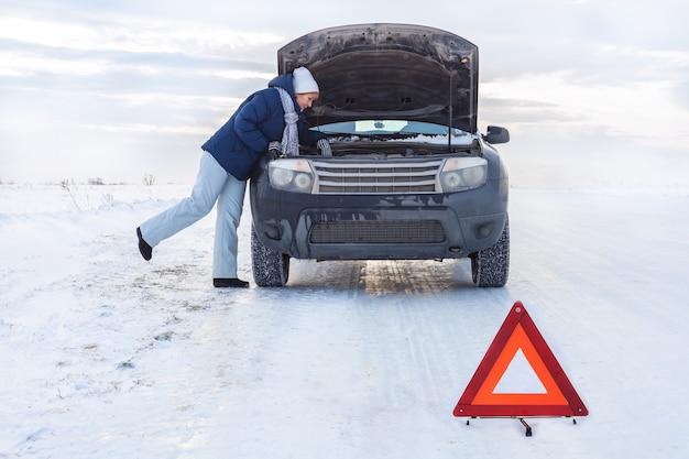 Une femme près de la voiture cassée en regardant le moteur. autour de l'hiver et du champ de neige. il y a un panneau d'urgence.