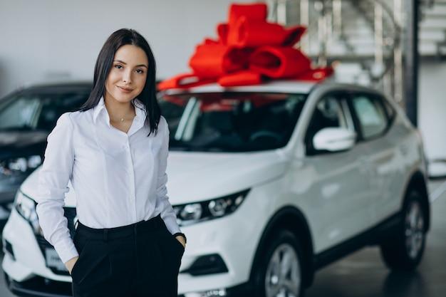 Femme près de la voiture avec grand arc rouge