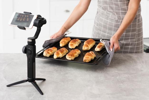 Femme présentant des pâtisseries devant la caméra