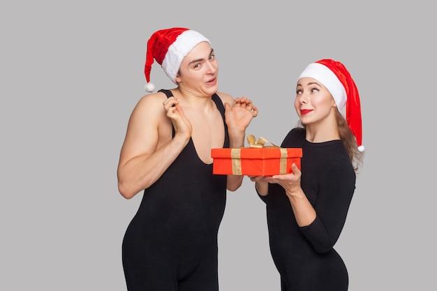 Femme présente boîte cadeau homme en bonnet de noel. homme aux bras levés regardant la caméra avec un visage surpris. notion de nouvel an. studio shot, isolé sur fond gris