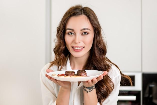 Femme présente un plat de viande qu'elle a cuisiné dans la cuisine