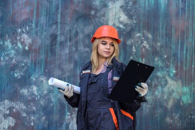 Une femme avec un presse-papiers en uniforme prend des réparations dans sa maison. concept de rénovation