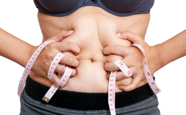 Femme presser le ventre avec du ruban à mesurer