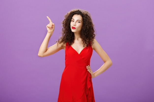 Femme prête à briller sur la piste de danse en élégante robe rouge avec maquillage sensuel et coiffure frisée poi...
