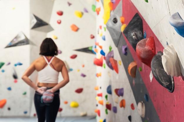 Femme prête à pratiquer l'escalade sur mur artificiel à l'intérieur. mode de vie actif et concept de bloc.