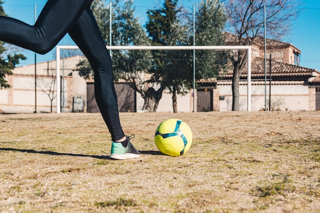 Femme prête à tirer un coup franc dans le but. terrain de football au sol.