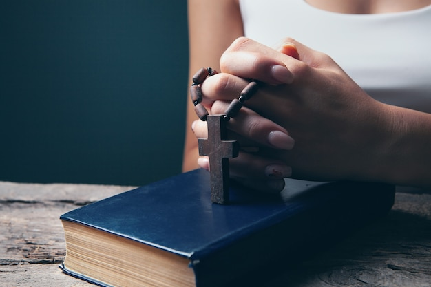Femme priant sur book holding cross