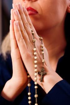 Femme priant avec chapelet à dieu