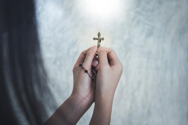 Femme priant avec crucifix dans l'église