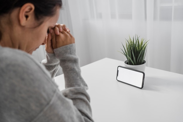 Femme priant à la maison avec smartphone