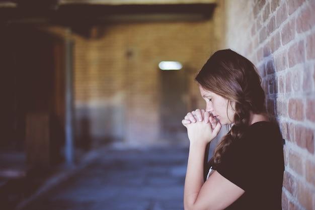 Femme priant en s'appuyant contre le mur de briques