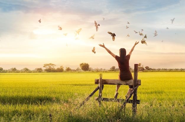 Femme, prier, et, oiseau libre, apprécier, nature, sur, coucher soleil, fond, espérer, concept
