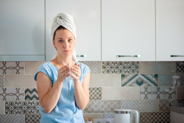 Une femme a pris une douche le matin et boit du café avec une serviette sur la tête.