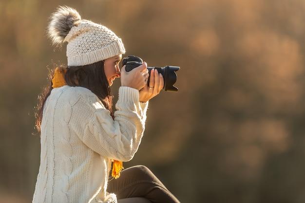 Femme de prise de vue photo dans un pull blanc et un chapeau à pompon par une journée froide.