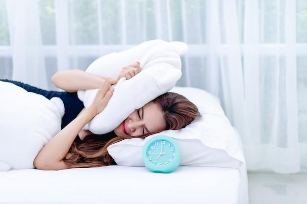 La femme prit l'oreiller de l'oreille pendant que le réveil sonne le matin