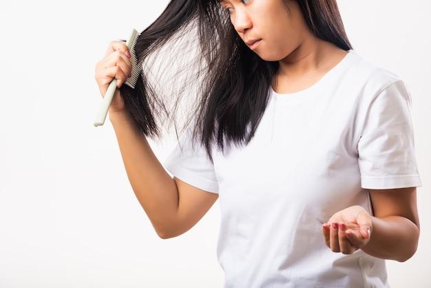 Femme problème de cheveux faibles, elle utilise une brosse à cheveux peigne brosse ses cheveux
