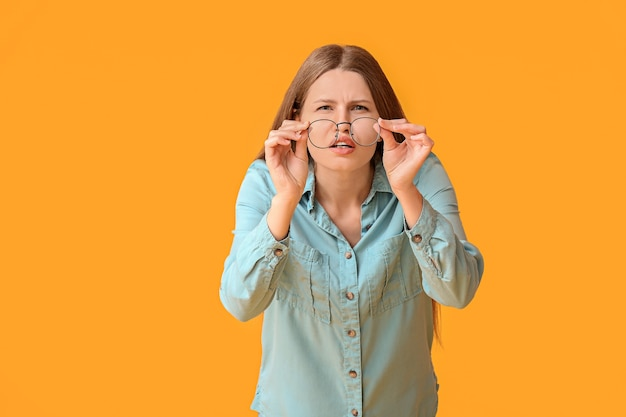 Femme avec problème de mauvaise vue sur la surface de couleur. symptômes du diabète