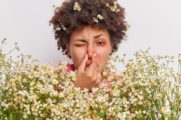 La femme a des problèmes respiratoires tient le nez souffre d'allergie à la camomille tient un gros bouquet de fleurs a les yeux rouges qui démangent