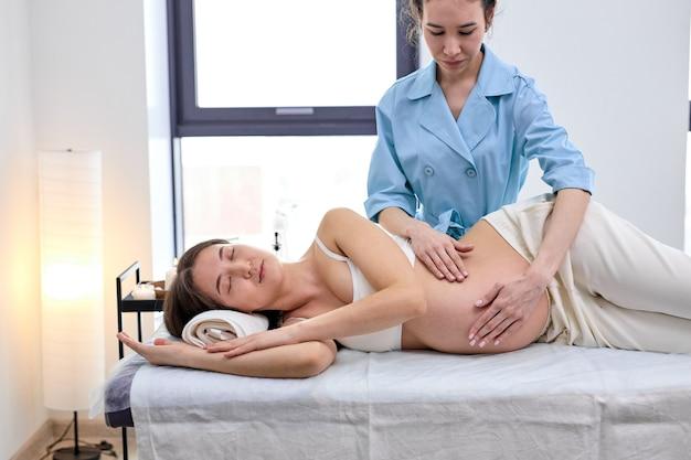 Femme professionnelle confiante faisant un massage à une femme enceinte, allongée sur le lit. problème de santé corporelle pendant la grossesse. journée relaxante. fermer. dans le salon du centre spa. photo en gros plan des mains