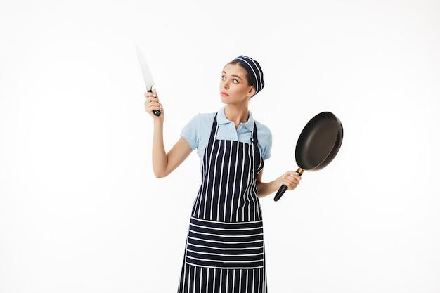 Femme professionnelle cuisinier en tablier rayé et casquette pensivement