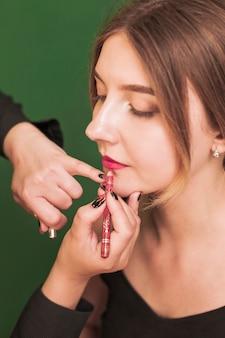 Femme professionnelle maquillant les lèvres de la fille