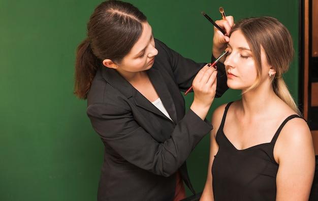 Femme professionnelle maquillant les yeux d'une fille