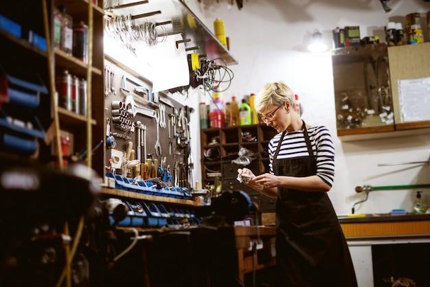 Femme professionnelle travailleuse, polissage de l'équipement de vélo dans l'atelier.