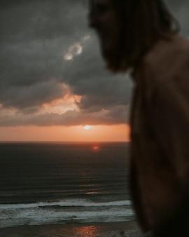 Femme profitant du lever du soleil sur la falaise à la plage