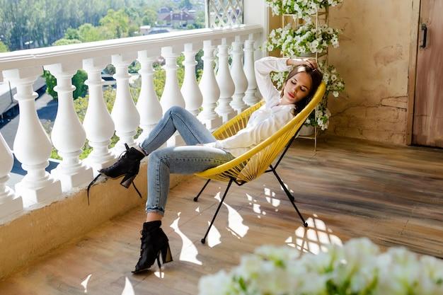 Femme profitant de sa confortable terrasse fleurie. jeune femme allongée sur une chaise, se détendre à la maison.