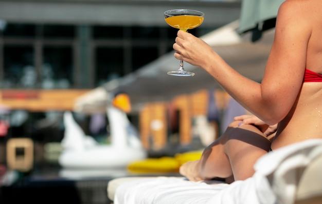 Femme profitant de sa journée à la piscine avec cocktail