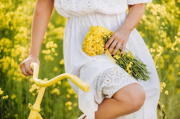 Une femme profite d'une balade à vélo à travers un champ plein de colza jaune vif avec un
