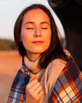 Femme de profiter du soleil avec une couverture tout en dehors dans la nature