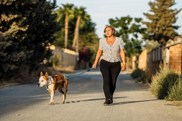 Femme promenant un chien dans une rue non pavée