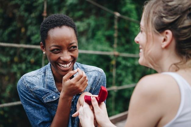 Femme proposant à sa copine heureuse en plein air l'amour et le concept de mariage