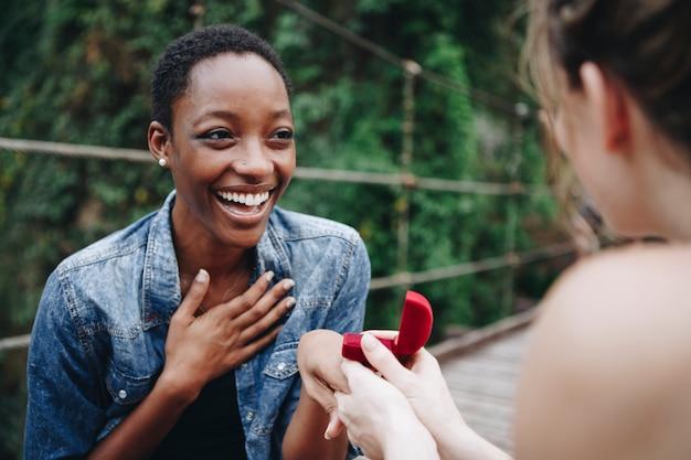 Femme proposant à sa petite amie heureuse l'amour en plein air