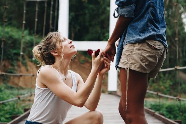 Femme proposant à sa petite amie heureuse à l'extérieur l'amour et le concept de mariage