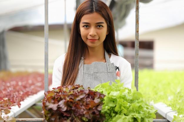 La femme propriétaire de la ferme maraîchère hydroponique elle et les légumes bio