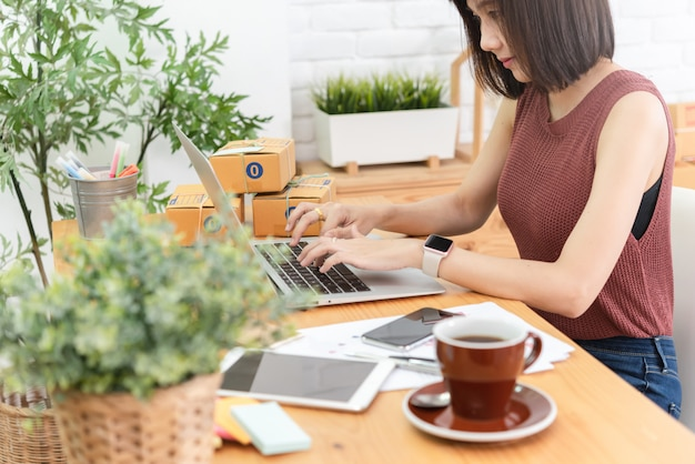Femme propriétaire de petite entreprise, démarrage d'entreprise conceptuelle, jeune entrepreneur travaille avec un ordinateur portable vend un produit en ligne boutique