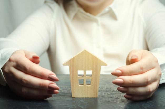 Une femme protège une maison en bois miniature.