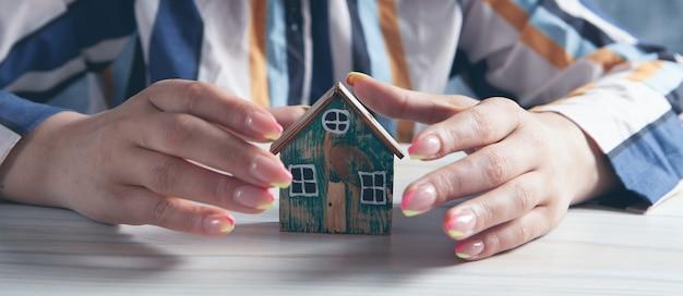 La femme protège la maison près de la table